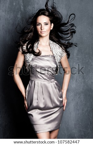 elegant woman in silver dress with long black flying hair studio shot