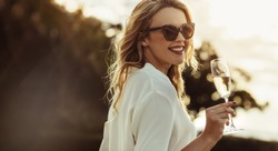 Elegant woman in sunglasses with a glass of wine outdoors. Smiling caucasian female having wine and looking backwards.