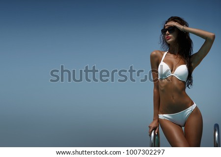 Elegant woman in the white bikini on the sun-tanned slim body is posing near the swimming pool in a good hot weather