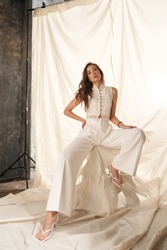 Elegant woman in white clothes sitting against white textile background. Fashion portrait. Lady wearing palazzo pants and lace blouse