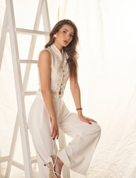 Elegant woman in white clothes sitting on white stairs in bright interior against textile background. Fashion portrait. Lady wearing palazzo pants and lace blouse