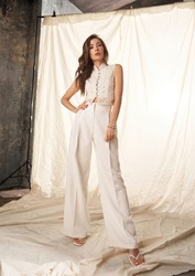 Elegant woman in white clothes standing against white textile background. Fashion portrait. Lady wearing palazzo pants and lace blouse