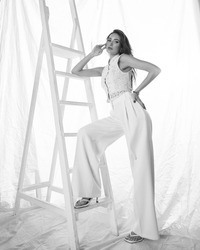 Elegant woman in white clothes standing leaning on white stairs in bright interior against textile background. Fashion portrait. Lady wearing palazzo pants and lace blouse