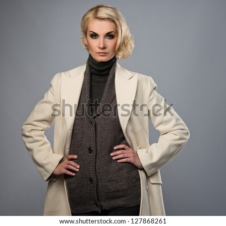 Elegant woman in white coat isolated on grey