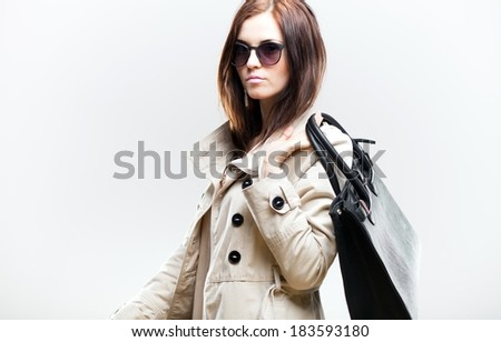 Elegant woman in white coat with black leather bag
