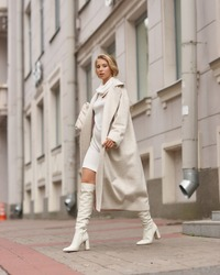 Elegant woman in white dress, hessian boots and coat walking at city street. Fall autumn fashion look. Pretty tall stylish young girl with fashionable makeup and hair style. Full length portrait