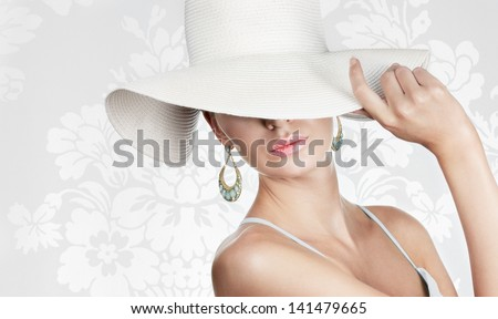Elegant woman in white hat on white fancy background Space for text