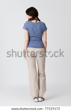 Elegant woman of Asian, rear view full length portrait isolated on gray studio background.