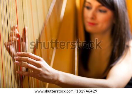 Elegant woman playing the harp  #181946429