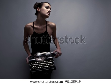 Elegant woman pose with ancient typewriter. Conceptual fashion photo.