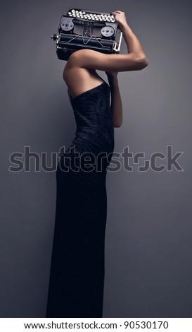 Elegant woman pose with ancient typewriter. Conceptual fashion photo.
