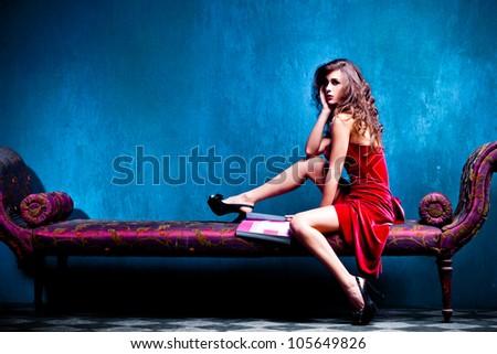 elegant woman sit on recamier reading magazine, studio shot, full body shot