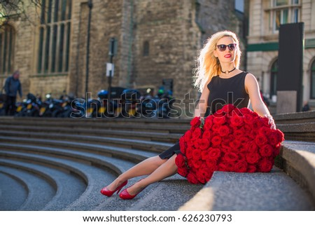 Elegant woman sits on the stairs with big bouquet of red roses, outdoors #626230793