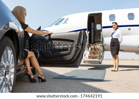 Elegant woman stepping out of car parked in front of private plane and airhostess