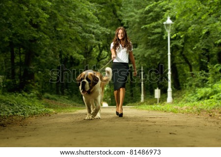 Elegant woman walking her big dog in the park
