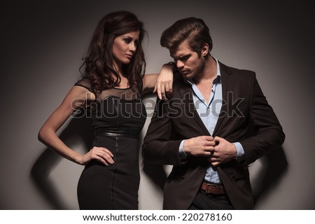 Elegant woman wearing a black dress looking and leaning on her boyfriend while the man is unbuttoning his brown jacket. Both looking away from the camera.