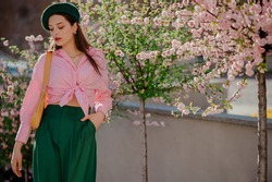 Elegant woman wearing stylish green beret, trousers, pink shirt with knot, yellow bag, posing near blooming sakura tree. Spring fashion, lifestyle conception. Copy, empty space for text