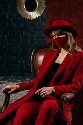 Elegant woman wearing stylish total red look with red protective face mask, hat, coat, trousers, posing, sitting on chair
