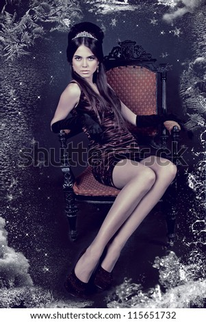 Elegant woman with fashion hair style sitting on vintage armchair in dark interior
