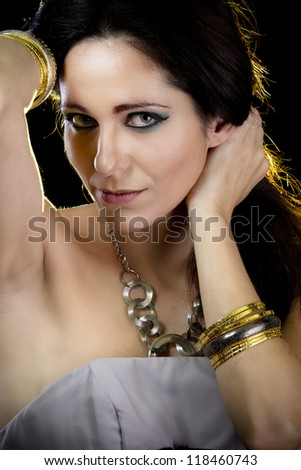 Elegant woman with golden light, gold and silver jewelry