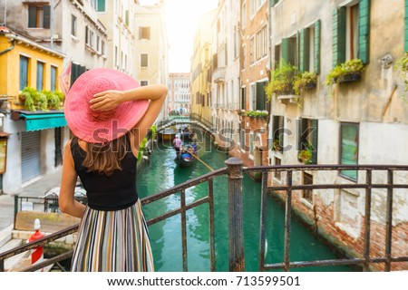 Elegant woman with red sunhat enjoys the view to a canal with passing by gondola in Venice, Italy Foto stock ©