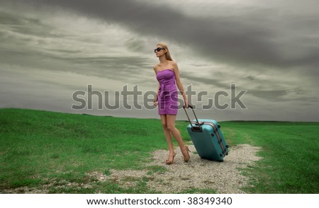 elegant woman with trolley lost in the countryside