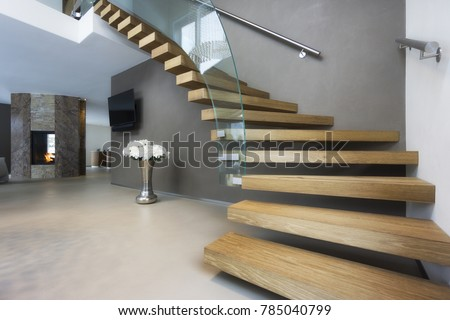 elegant wood and glass staircase in luxury home #785040799