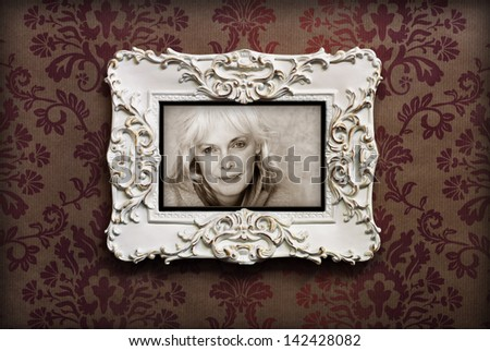 Elegant wooden frame with sepia toned casual portrait of happy mature woman on Victorian style wallpaper.