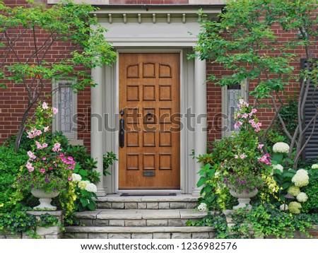 elegant wooden front door surrounded by flowers #1236982576