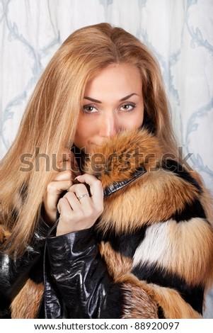 Elegant young brunette woman in stylish fur coat
