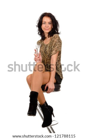 Elegant young brunette woman with a glass of champagne in her hand sitting on a contemporary bar stool isolated on white