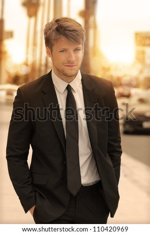 Elegant young businessman walking in the city in golden morning light