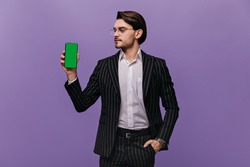 Elegant young businessman with brunette hair, white shirt, classic striped suit and glasses, looking aside at phone in one hand and posing isolated over violet background