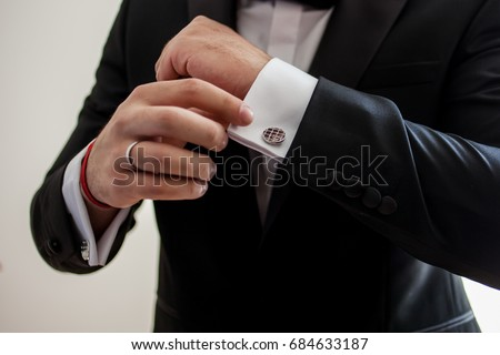 Elegant young fashion man looking at his cufflinks while fixing them. Black and white photo of male hands. Handsome groom dressed in black formal suit, white shirt and tie is getting ready for wedding