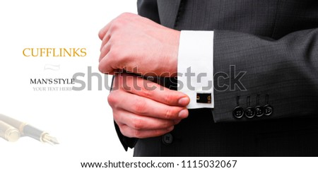 Elegant young fashion man looking at his cufflinks while fixing them.  Creative layout man in black jacket holds cufflinks on isolated background.  Flat lay. Your text here.