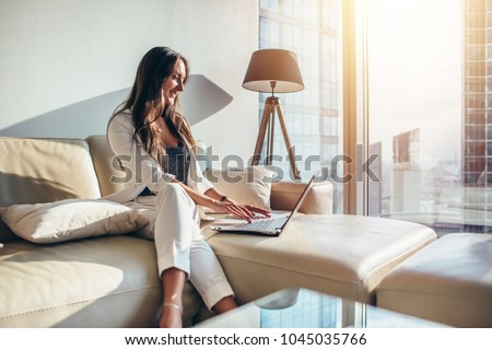 Elegant young female business woman using a laptop sitting on a sofa at home ストックフォト ©