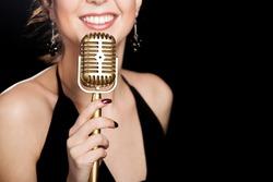 Elegant young female singer in black dress smiling holding golden vintage microphone, live performance, concert, unrecognizable person, close up, focus on mic, copy space. Black background