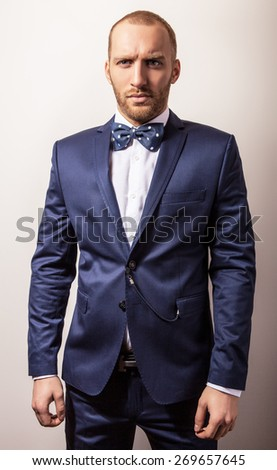 Elegant young handsome man in dark blue costume & bow tie. Studio fashion portrait.