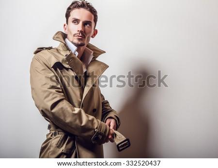 Elegant young handsome man in long stylish coat. Studio fashion portrait.