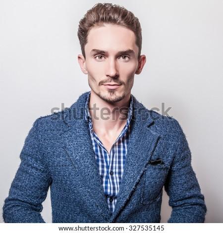 Elegant young handsome man in stylish blue jacket. Studio fashion portrait.  #327535145