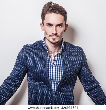 Elegant young handsome man in stylish dark blue jacket. Studio fashion portrait.  #326931521