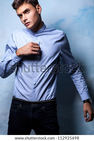 Elegant young handsome man on grunge background. Studio fashion portrait.
