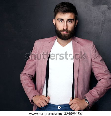 Elegant young handsome man posing in studio, looking at camera. Man with beard.