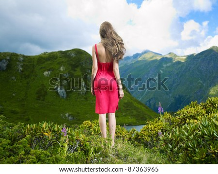 Elegant young lady in a red dress on a mountain meadow flower