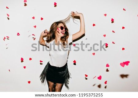 Elegant young lady in trendy sunglasses looking up at fallen hearts. Portrait of positive long-haired woman in short skirt enjoying photoshoot. #1195375255