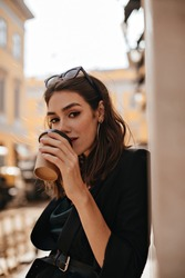 Elegant young lady with brunette wavy hair, modern makeup and black jacket, drinking cup of coffee at city cafe terrace and looking straight