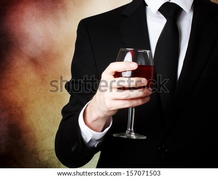 Elegant young man holding a glass of red wine
