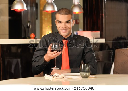Elegant young man holding glass of red wine. Man tasting red wine in restaurant
