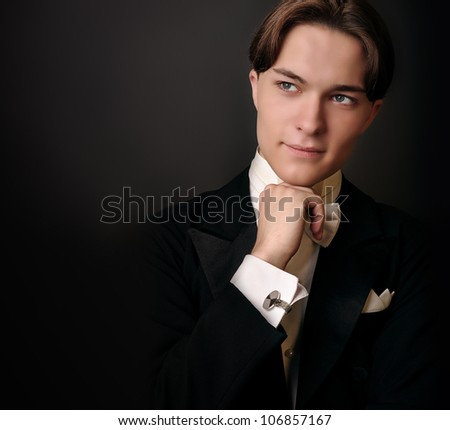 Elegant young man in suit and butterfly-tie staring