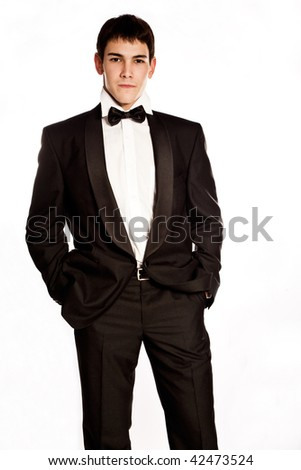 elegant young man in tuxedo, studio on white - stock photo